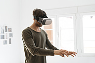 Young man wearing virtual reality glasses at home - KKAF00298