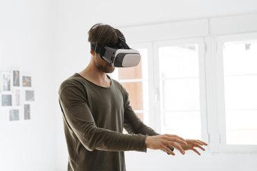 Young man wearing virtual reality glasses at home - KKAF00298