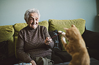 Smiling senior woman playing with her kitten at home - RAEF01636