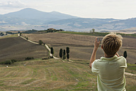 Italy, Tuscany, Boy taking pictures of landscape - PAF01747