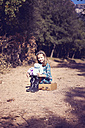 Portrait of girl sitting on a vintage suitcase - XCF00124