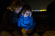 Mother and son using cell phone at night - SIPF01279