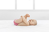 Happy baby playing around girl on white bed - LITF00481