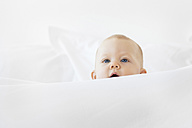 Baby girl peeking over white bed sheet - LITF00490