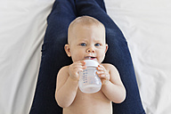 Little girl lying on mother's lap, drinking from baby bottle - LITF00493