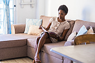 Young woman sitting on the couch reading magazine - SIPF01286