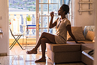 Young woman sitting on the couch drinking glass of red wine - SIPF01289