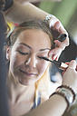 Stylist applying mascara on woman's eyelashes - ASCF00680