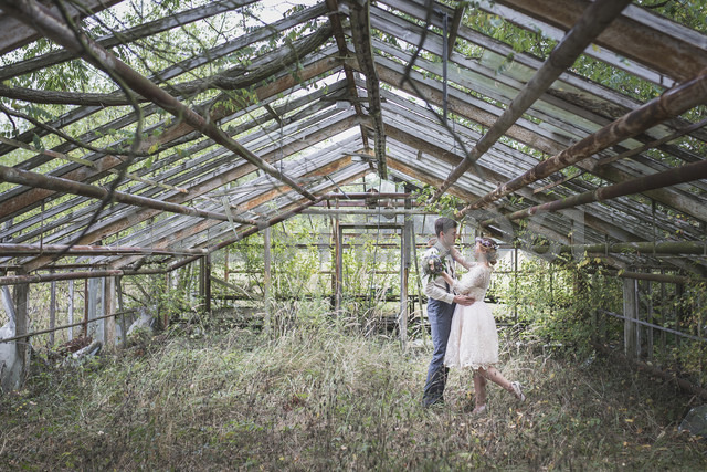 Bride and groom embracing in greenhouse - ASCF00683