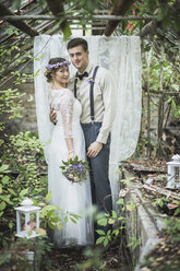 Bride and groom embracing in greenhouse - ASCF00689