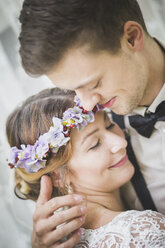 Close-up of bride and groom embracing - ASCF00692
