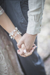 Close-up of bride and groom holding hands - ASCF00698