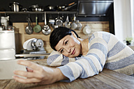 Woman in kitchen resting on table holding cell phone - FMKF03454