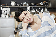 Portrait of smiling woman in kitchen - FMKF03457