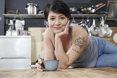 Portrait of smiling woman in kitchen with cup of coffee - FMKF03463