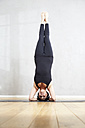 Woman practising yoga doing a headstand - FMKF03472