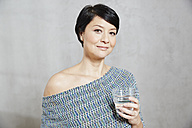 Portrait of confident woman holding glass of water - FMKF03475