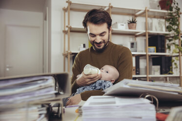 Father feeding his baby in home office - MFF03429