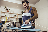 Father ironing and carrying his baby at home - MFF03438