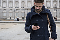 Man with a coat and bag using his phone - ABZF01792