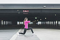 Woman stretching at parking garage - ASCF00707