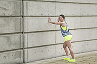 Woman stretching at building - ASCF00710