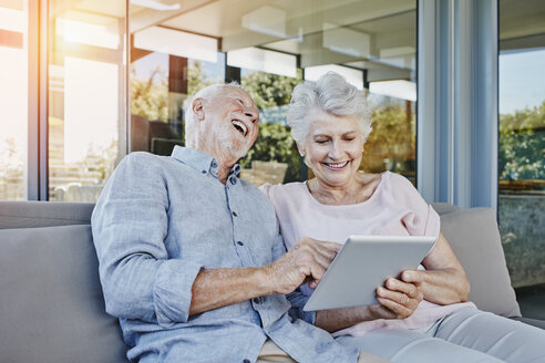 Senior couple sitting on terrace using digital tablet - RORF00443