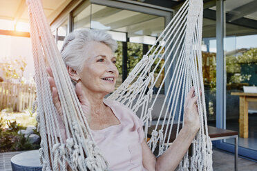 Senior woman sitting in hammock on terrace - RORF00446