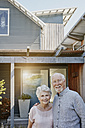 Senior couple standing in front of their house, looking confident - RORF00449