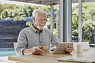 Senior man sitting on terrace, doing online payment with credit card - RORF00464