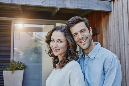 Couple standing in front of door of their home - RORF00470