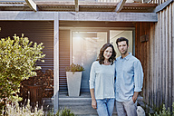 Couple standing in front of door of their home - RORF00473