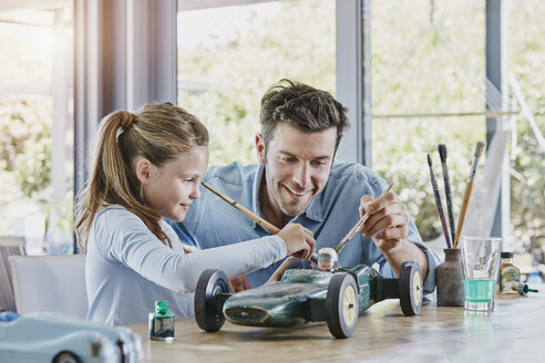 Father and daughter painting a toy race car - RORF00479