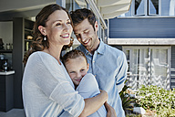 Happy family standing on terrace, embracing daughter - RORF00494