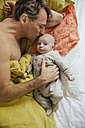 Father cuddling in bed with his newborn baby - MFF03452