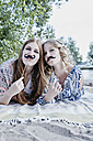 Portrait of two teenage girls with paper moustaches lying on blanket on the beach - RORF00525