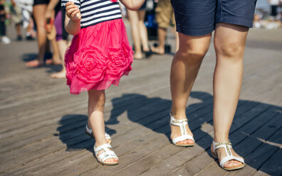 USA, New York, Coney Island, mother and little daughter walking on wooden walkway, partial view - DAPF00549