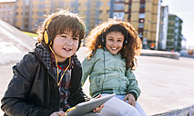 Two children listening music with headphones and tablet - MGOF02794