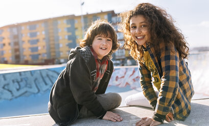Portrait of two children sitting on a wall - MGOF02803
