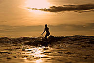 Indonesia, Bali, silhouette of woman surfing at sunset - KNTF00606