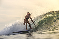 Indonesia, Bali, woman surfing at sunset - KNTF00609