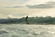Indonesia, Bali, woman surfing at sunset - KNTF00612