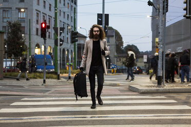 Stylish young man with bag crossing street on zebra crossing - MAUF00954