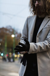 Stylish young man outdoors putting on gloves - MAUF00957