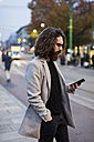Stylish young man in the city checking cell phone - MAUF00960