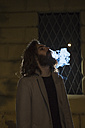 Stylish young man smoking outdoors at night - MAUF00978