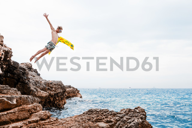 Man with airbed jumping from rock into the sea - WVF00773 - Valentin Weinhäupl/Westend61