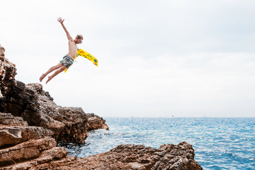 Man with airbed jumping from rock into the sea - WVF00773