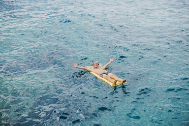 Happy young man relaxing on airbed in the sea - WVF00776