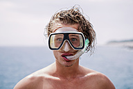 Portrait of young man with diving goggles and snorkel pulling funny faces - WVF00779